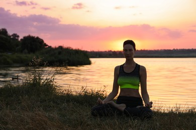 Mature woman meditating near river at sunset. Space for text