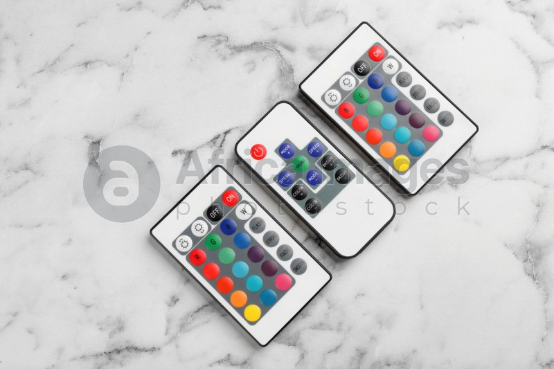 Remote controls on white marble table, flat lay