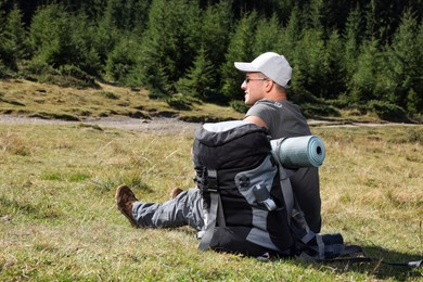 Man with backpack and sleeping mat near forest