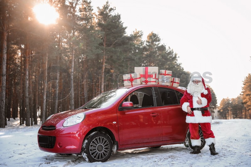 Authentic Santa Claus near red car with gift boxes, outdoors