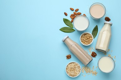 Different vegan milks and ingredients on light blue background, flat lay. Space for text