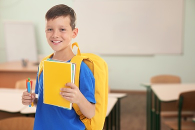 Little boy with school stationery in empty classroom
