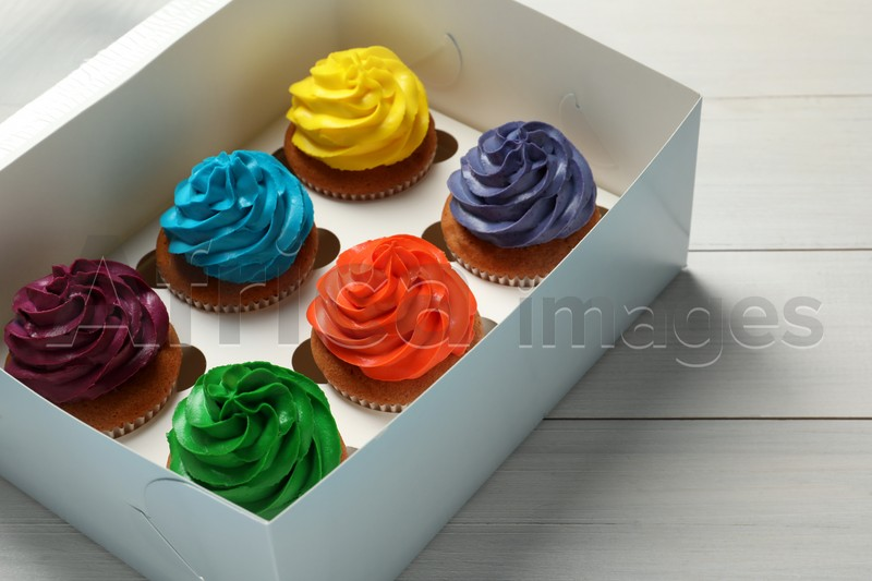 Box with different cupcakes on white wooden table, closeup