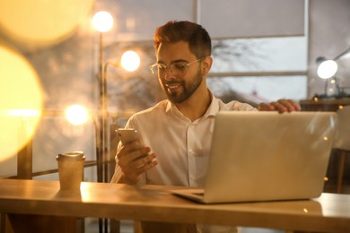 Man using smartphone while working with laptop in office