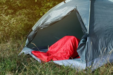 Red sleeping bag in camping tent on green grass outdoors