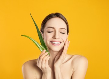 Happy young woman with aloe leaves on yellow background