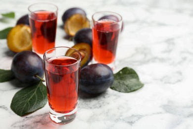 Delicious plum liquor and ripe fruits on white table. Homemade strong alcoholic beverage