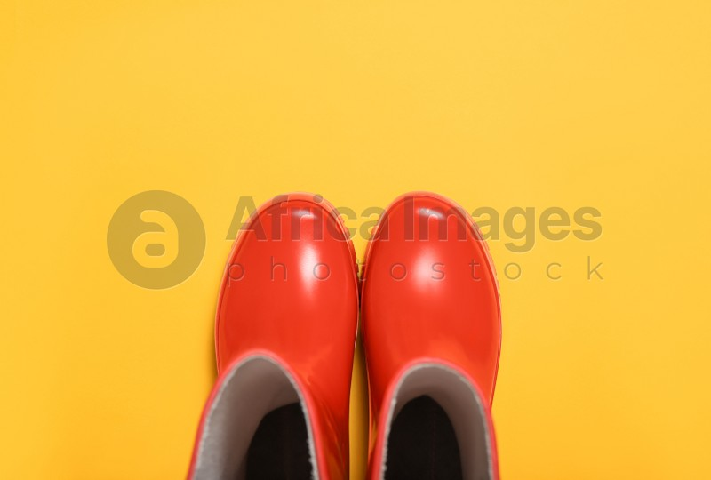 Red rubber boots on orange background, top view