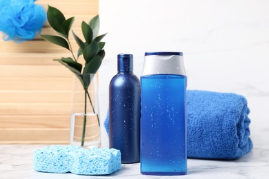 Cosmetic products and towel on white marble table. Men's hygiene