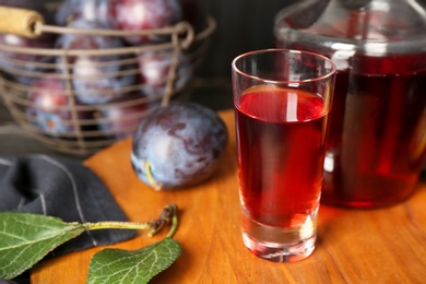 Delicious plum liquor in shot glass on wooden board. Homemade strong alcoholic beverage
