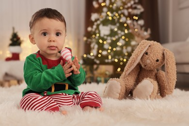Baby wearing cute elf costume on floor in room decorated for Christmas