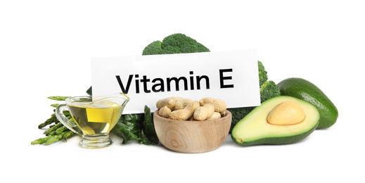 Card with phrase Vitamin E and different products on white background