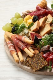 Different tasty appetizers on white wooden table, closeup