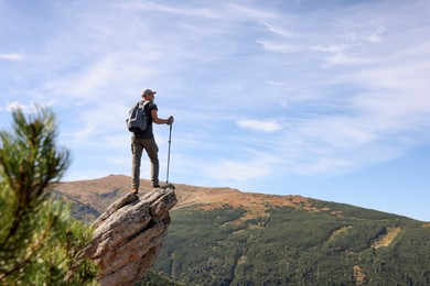 Man with backpack and trekking poles on rocky peak in mountains, back view