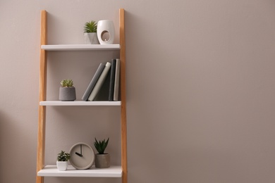 Plants and accessories on decorative ladder near grey wall indoors, space for text