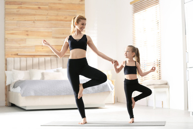 Mother and daughter in matching sportswear doing yoga together near bed at home