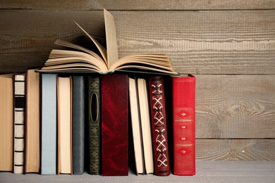 Different hardcover books on grey wooden table