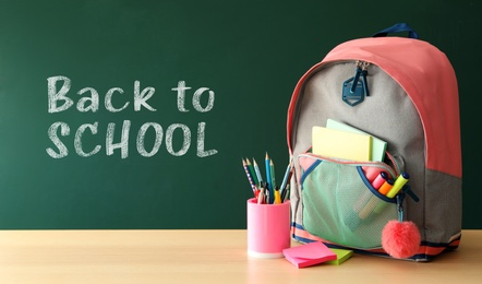 Backpack and different stationery on wooden table near green chalkboard with text Back To School