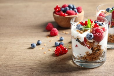 Tasty dessert with yogurt, berries and granola on wooden table. Space for text