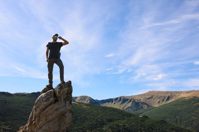 Man enjoying picturesque view on cliff in mountains. Space for text