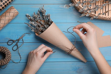 Woman making beautiful bouquet of pussy willow branches at light blue wooden table, top view