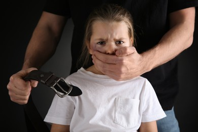 Man with belt covering scared little girl's mouth on black background. Domestic violence
