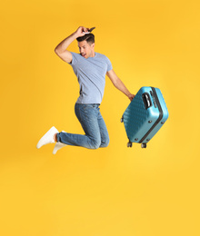 Handsome man with suitcase for summer trip jumping on yellow background. Vacation travel