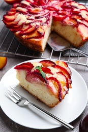 Slice of delicious cake with plums on table, closeup