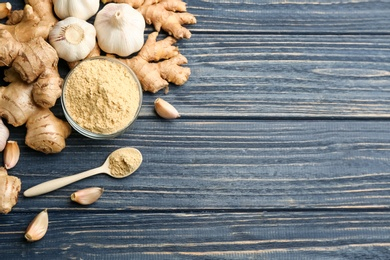 Fresh garlic, ginger roots and powder on blue wooden table, flat lay with space for text. Natural cold remedies