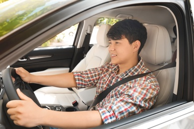 Male driver with fastened safety belt in car