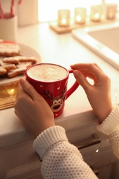 Woman holding cup with hot drink in kitchen, closeup