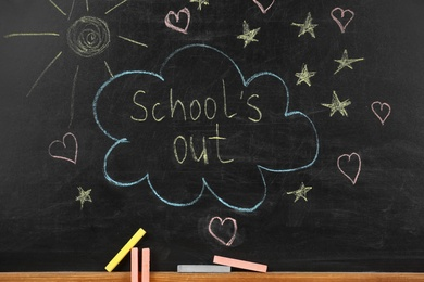 Pieces of color chalk near blackboard with text School's Out. Summer holidays