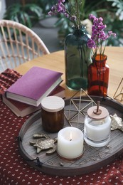 Wooden tray with decorations and books on table indoors