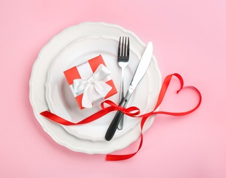 Beautiful table setting for Valentine's Day dinner on pink background, flat lay