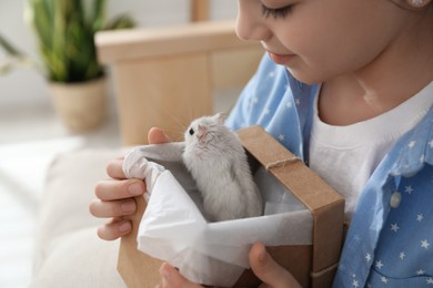 Happy little girl holding gift box with cute hamster at home
