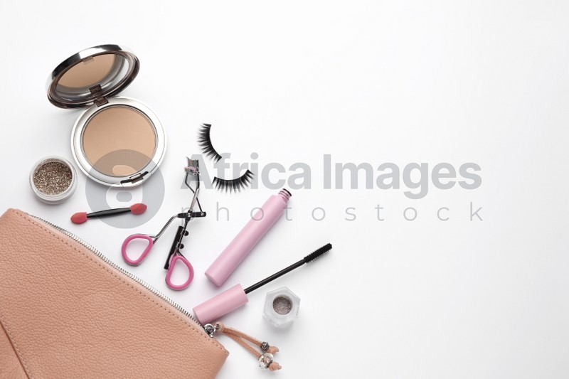 Composition with eyelash curler and makeup products on white background, top view