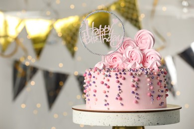 Beautifully decorated birthday cake on stand against blurred festive lights. Space for text