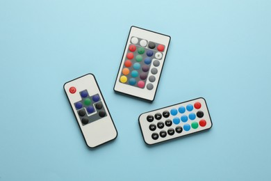 Different remote controls on light blue background, flat lay