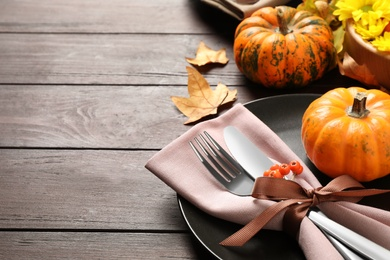 Festive table setting with autumn decor and space for text on wooden background, closeup. Thanksgiving Day celebration