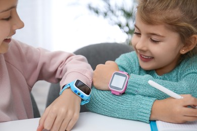 Girls with stylish smart watches at table indoors, closeup