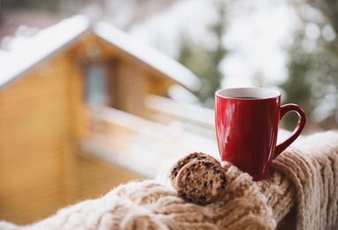 Fresh coffee, tasty cookies and knitted fabric outdoors on winter morning. Space for text