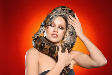 Beautiful woman with boa constrictor on bright colorful  background