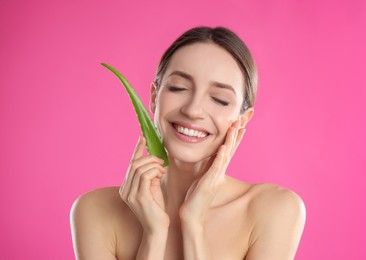 Happy young woman with aloe leaf on pink background