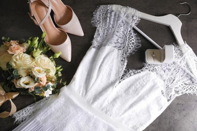 Flat lay composition with white wedding dress on grey stone table