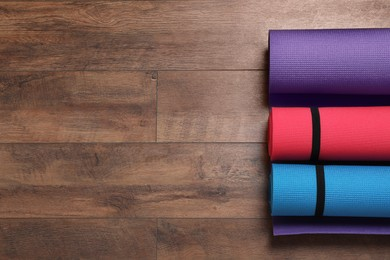 Bright rolled camping mats on wooden background, flat lay. Space for text