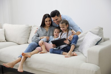 Family with tablet sitting on comfortable sofa in living room