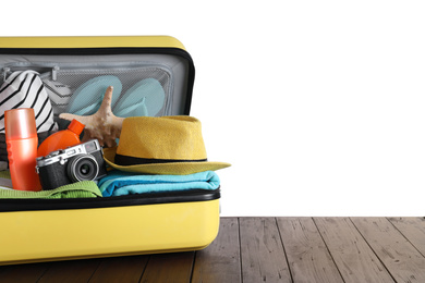 Open suitcase with different beach objects on wooden table against white background. Space for text