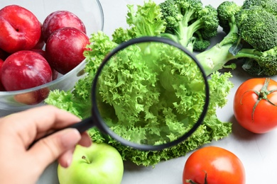 Woman with magnifying glass exploring vegetables and fruits, closeup. Poison detection