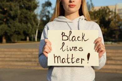 Young woman holding sign with phrase Black Lives Matter outdoors, closeup. Racism concept