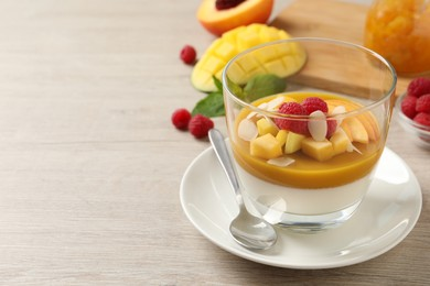 Delicious panna cotta with mango coulis, fresh fruit pieces and almond flakes on light wooden table. Space for text